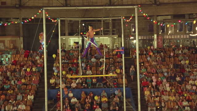 wide angle of male trapeze artist. see crowd in background. see him swing on trapeze towards pov, release and flip then fall. see crowd stand and look worried. audiences. circus. stunt. acrobat. - akrobat stock-videos und b-roll-filmmaterial