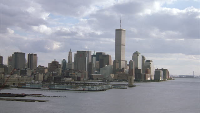 vídeos de stock e filmes b-roll de aerial over hudson river moving toward skyscrapers of lower manhattan or new york city skyline. see world trade center twin towers. - world trade center manhattan
