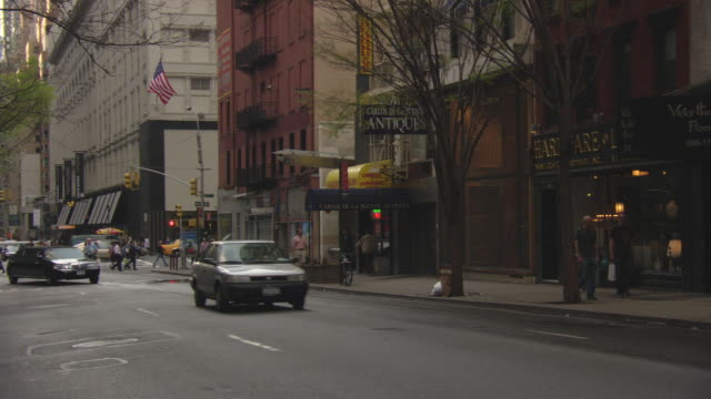 vídeos de stock, filmes e b-roll de wide angle of black limo driving down one way street. see antique shop and hardware store in background. camera follows limo down street. see marquee and queensboro bridge in background. manhattan. upper east side. - antiquário loja