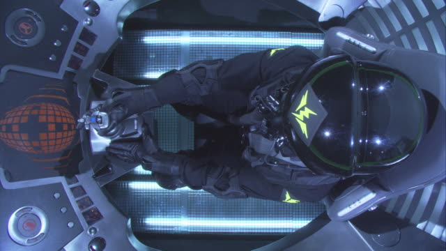high angle down of stunt person in black space or astronaut suit. see pilot in cockpit of futuristic space ship, rocket, or jet. see helmet with yellow lightning bolt stickers. dashboards. - 宇宙航空機点の映像素材/bロール