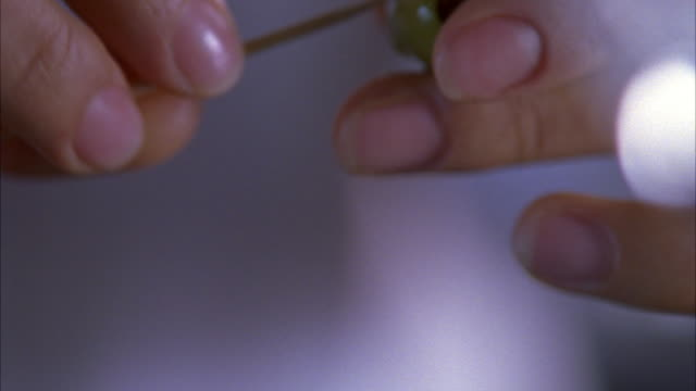 close angle of woman's hands holding napkin. wipes hands with napkin then spears two green olives with toothpick and places them into a martini. - martini glass stock videos & royalty-free footage