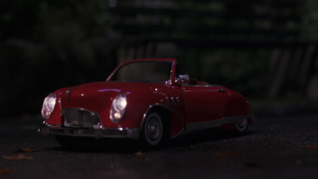MEDIUM ANGLE OF RED REMOTE CONTROL CONVERTIBLE CAR WITH LIGHTS ON. SEE DRIVER DOOR OPEN, CAMERA ZOOMS IN TO DOOR. SEE DOOR CLOSE. SEE PAVEMENT AND BUSHES IN BACKGROUND.