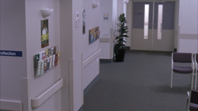 """medium angle of hospital hallway with plant, chair, medical pamphlets, sign reading """"specimen collection."""" - pamphlet stock videos & royalty-free footage"""