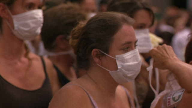 stockvideo's en b-roll-footage met medium angle of men and women in crowd putting on medical or dust masks. see crowd extending far into background. - protective workwear