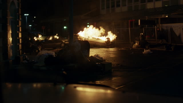 medium angle, moving pov of urban area with cars in flames. camera moves around corner, stops where car fires barricade street between buildings. riots. - ribellione video stock e b–roll