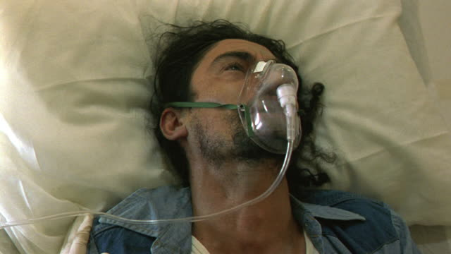 medium angle of man in lying on hospital bed with oxygen mask. man starts coughing, nurse gives aid. - oxygen mask stock videos and b-roll footage