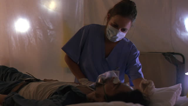 MEDIUM ANGLE OF MAN IN LYING ON HOSPITAL BED WITH OXYGEN MASK. MAN STARTS COUGHING, WOMAN NURSE IN RESPIRATOR MASK AND BLUE SCRUBS GIVES AID.