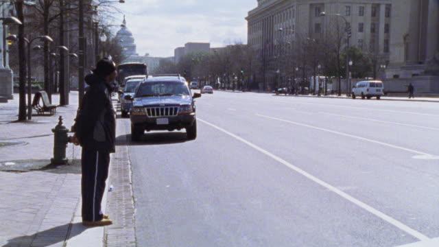 vídeos y material grabado en eventos de stock de est ms curb. see capitol hill in bg. dark jeep grand cherokee pulls up to curb and parks. see pedestrian passing in fg. city street. - edificio del capitolio washington dc