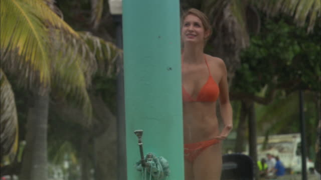 medium angle of bikini-clad woman standing at outdoor pool or beach shower. - bikini stock videos and b-roll footage