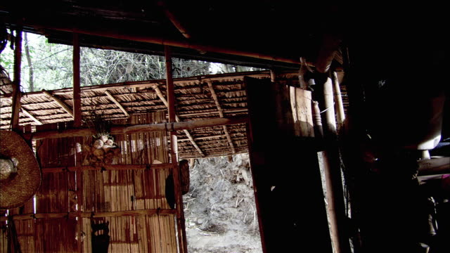 medium angle of makeshift home or tent interior, cluttered piles of stuff in baskets, walls made of bamboo and chicken wire wall. - chicken wire stock videos and b-roll footage