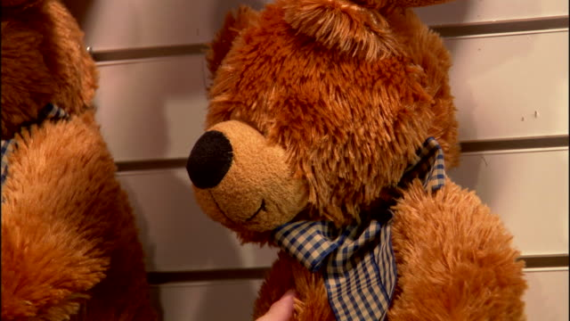 CLOSE ANGLE OF BROWN PLUSH STUFFED BEARS OR TOYS ON DISPLAY AT CARNIVAL OR FAIR BOOTH. SEE FOREHEAD OF MAN.