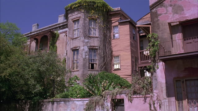 pull back of street with vintage car, three story house or apartment building with brick walls, octagonal bay window rooms, ivy on side.  a bit rundown.  could be lower class. shot tilts up as it dollies in. - erkerfenster stock-videos und b-roll-filmmaterial