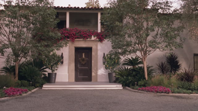 wide angle of upper class house, brick driveway, trees, lawn, yard, silver car arriving. could be brentwood or beverly hills. - https点の映像素材/bロール