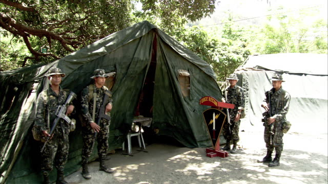 wide angle of tent military camp command post. soldiers in camouflage fatigues stand guard with rifles, others walk past. sign reads 'force recon.' - military camp stock videos & royalty-free footage