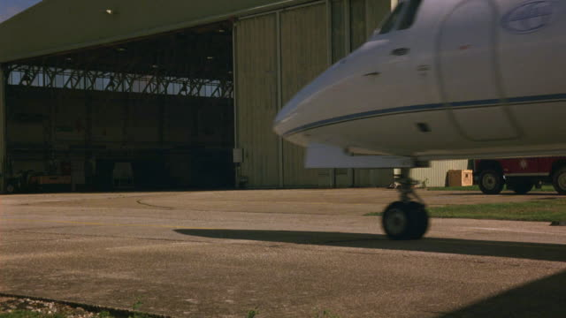 wide angle of private jet taxi past pov on tarmac then turn and park in airplane hangar. plane is hawker siddeley hs 125-700b. runways. planes. airports. - airplane hangar stock videos and b-roll footage