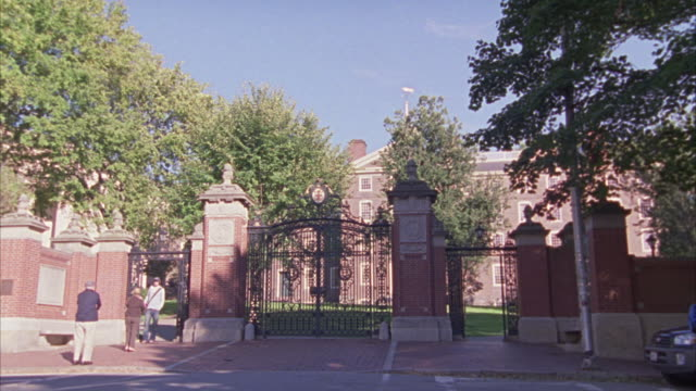 WIDE ANGLE OF A GATE FOR A PRIVATE SCHOOL, UNIVERSITY, OR COLLEGE CAMPUS.  MADE OF BRICKS AND WROUGHT IRON.  LOOKS UPPER CLASS. STUDENTS WALK PAST.