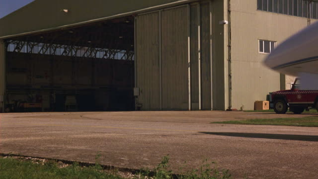 wide angle of private jet taxi past pov on tarmac then turn and park in airplane hangar. plane is hawker siddeley hs 125-700b. runways. airports. - airplane hangar stock videos and b-roll footage