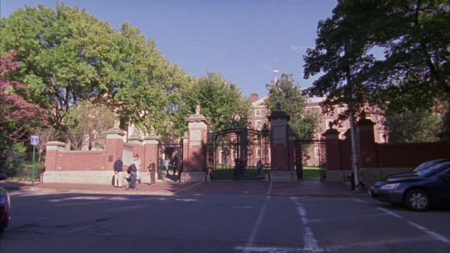 PULL BACK AND ZOOM IN ON A GATE FOR A PRIVATE SCHOOL, UNIVERSITY, OR COLLEGE CAMPUS.  MADE OF BRICKS AND WROUGHT IRON.  LOOKS UPPER CLASS. STUDENTS WALK PAST.