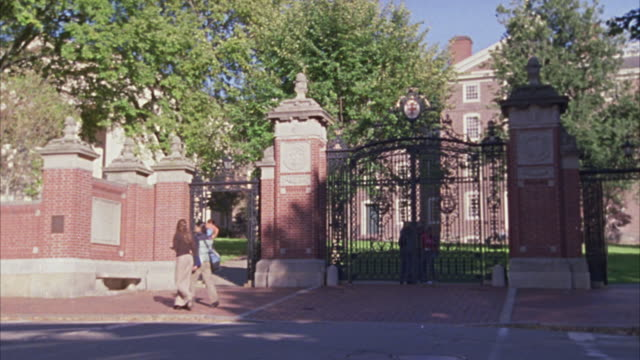 HAND HELD ANGLE OF A GATE FOR A PRIVATE SCHOOL, UNIVERSITY, OR COLLEGE CAMPUS.  MADE OF BRICKS AND WROUGHT IRON.  LOOKS UPPER CLASS. STUDENTS WALK PAST.