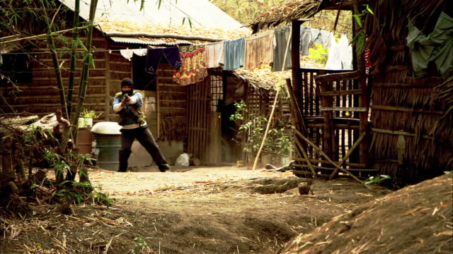 wide angle of several terrorists or insurgents or soldiers attempting to flee a jungle village. - man and machine stock videos & royalty-free footage
