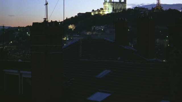 pan up from rooftops in residential area of european city. brick chimneys and dormer windows. church, cathedral. basilica of notre dame de fourviere on hilltop. - dormer stock videos and b-roll footage