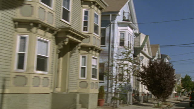wide angle driving pov of residential area with two story clapboard style victorian   houses. middle class neighborhood. narrow  urban lots. some houses have bay and dormer windows. a few small trees line sidewalk. - erkerfenster stock-videos und b-roll-filmmaterial
