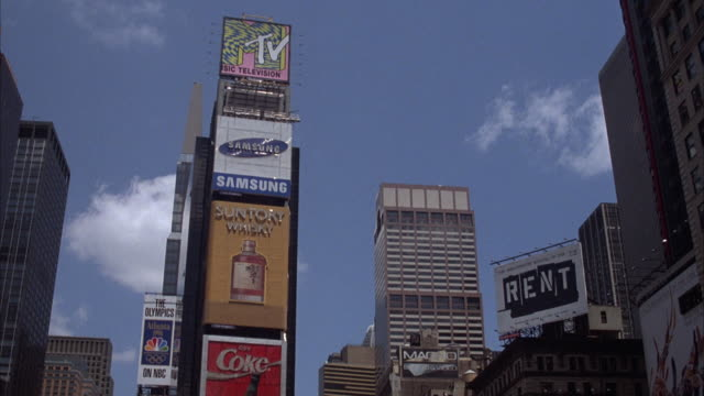 "vídeos y material grabado en eventos de stock de wide angle of times square with  building with neon signs of different companies, ""mtv,"" ""samsung,"" ""suntory,"" and ""coke."" ""rent"" billboard on right. - 1996"