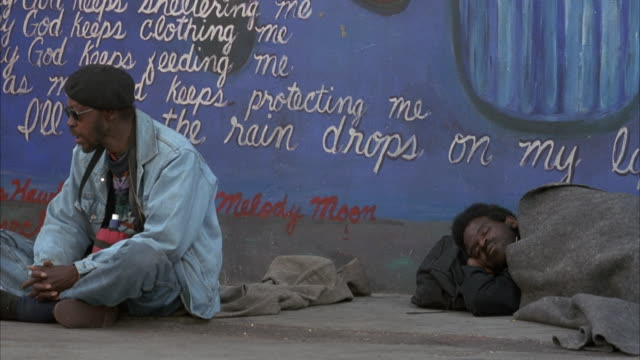 MEDIUM ANGLE OF TWO HOMELESS MEN BY GRAFFITI WALL BY SIDEWALK. PANS LEFT TO TWO STUDENTS CONVERSING. PANS BACK TO LEFT.