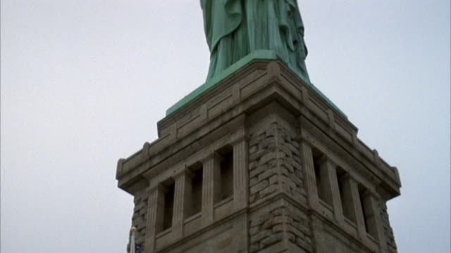 vidéos et rushes de pan up from stone base to top of statue of liberty. stops panning when all of statue is visible. pov is at base of statue looking up. see american flag hung on base in beginning. - statue de la liberté