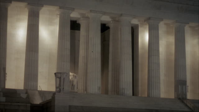 medium angle moving pov from drivers side of car passing front of lincoln memorial. see statue of lincoln between columns. memorial is lit by lights. - side lit stock videos & royalty-free footage