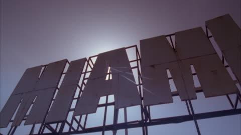 """vídeos y material grabado en eventos de stock de medium up angle of """"miami"""" sign, possibly on top of building. see sun halations through """"a"""", airplane flies across to top. - miami"""
