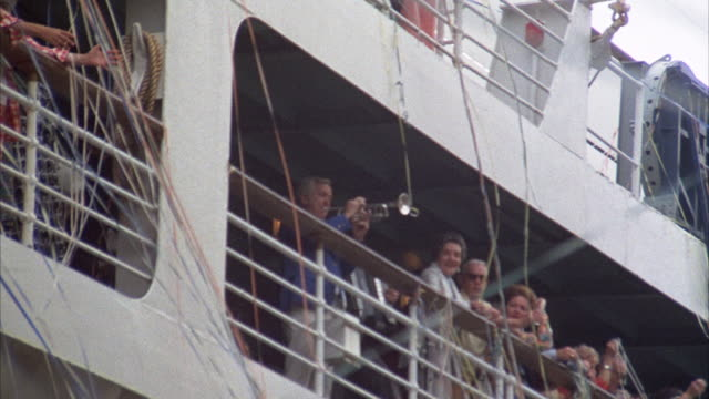 stockvideo's en b-roll-footage met up angle of people on cruise ship. see people standing near rails, man playing trumpet. see streamers falling from ship. - muzikant