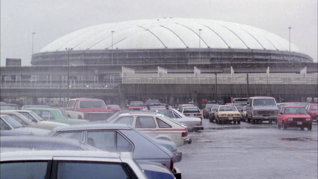 MEDIUM ANGLE OF BC PLACE STADIUM IN RAIN. PARKING LOT IN FOREGROUND WITH PARKED CARS. FREEWAY IN FRONT OF STADIUM WITH TRAFFIC MOVING ACROSS. COUPLE RUNS TOWARD STADIUM. NEG CUT.
