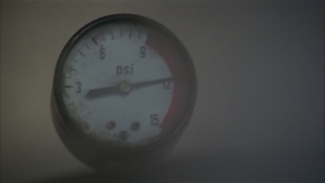 medium angle of gas pressure meter or gauge measuring in psi. see needle fluctuating and see smoke  or steam passing in front.could be used for a water heater, boiler or pressure cooker about to explode. - boiler stock videos & royalty-free footage