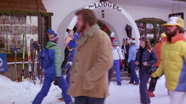 """MEDIUM ANGLE OF """"THE LODGE"""" ENTRANCE IN VAIL. SEE PEOPLE IN SNOW WEAR WALKING IN AND OUT OF ENTRANCE. SEE SKIS STUCK OUTSIDE IN SNOW. SKI RESORT."""