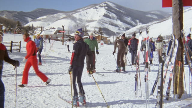 medium angle of skiers on ski hills. see several snow suit wearing skiers walk around. see  skis leaning against pole in foreground. buildings and mountains in background. could be ski lodge. - ski lodge stock videos & royalty-free footage