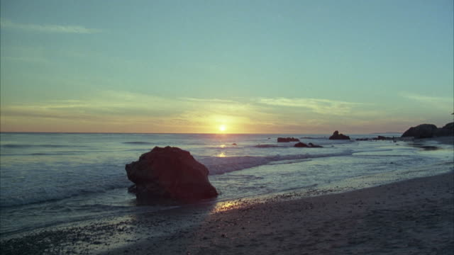 medium angle of beach sunset. see ocean and sun setting in distance. see large rock on sandy beach in foreground, larger rocks in background. zoom in to sun, see waves rolling. - california sunset stock videos & royalty-free footage