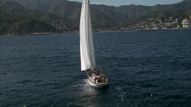 MEDIUM ANGLE OF SAILBOAT ON OCEAN HEADING RIGHT. CAMERA PANS RIGHT AND PULLS BACK, SEE CATALINA ISLAND SHORE IN FAR BACKGROUND.