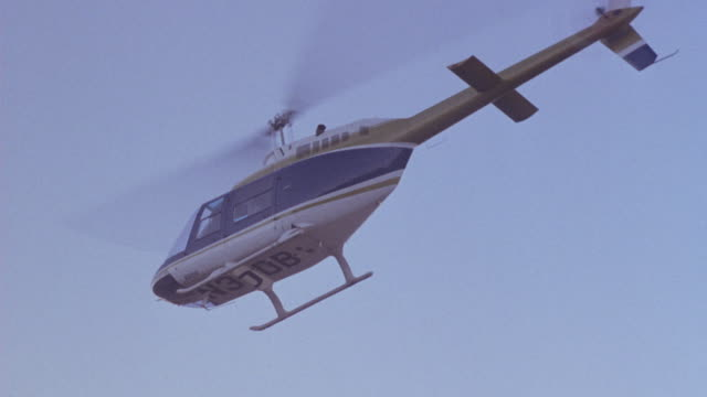 up angle of blue and gold helicopter. see helicopter fly over head. see sparks from helicopter. - ヘリコプター事故点の映像素材/bロール