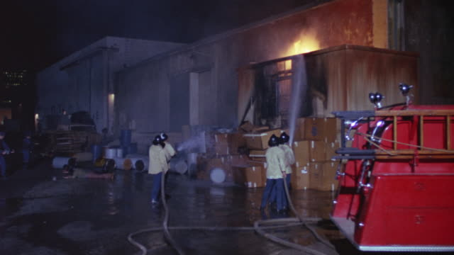 medium angle of four firefighters extinguishing fire with hose toward factory or industrial building on right. see two guards pointing guns toward building in left background. rear of fire truck in right foreground. - fire hose stock videos & royalty-free footage