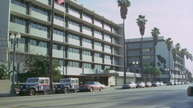 vidéos et rushes de pull back from sign in front of apartment building. see palm trees line sidewalk. could be hospital. - palmier