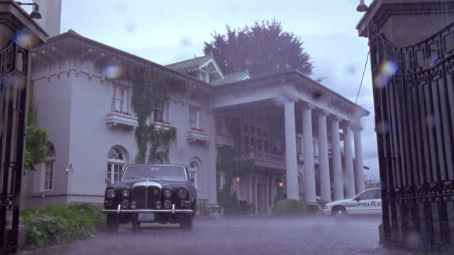 medium angle of mansion on rainy day. see classic mercedes or rolls royce parked in front of mansion. see police car also parked in front of mansion. - rolls royce stock videos and b-roll footage