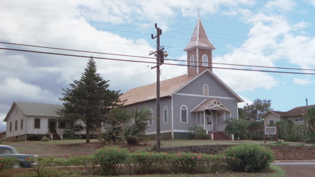 wide angle of church of chapel in small town or rural town. car drives past in front of camera from right to left. clouds moving in blue sky in background. - small town america stock videos and b-roll footage