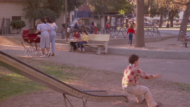 wide angle of children running around in playground during day. see two children sitting on bench in background. children taking turns on slide in foreground. - rutschen stock-videos und b-roll-filmmaterial
