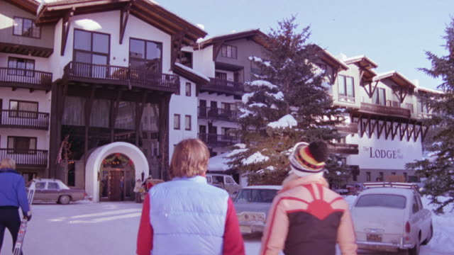 WIDE ANGLE OF ENTRANCE TO SKI RESORT LODGE. SEE PEOPLE DRESSED IN SKI GEAR WALKING TOWARDS ENTRANCE. SNOW COVERED GROUND.