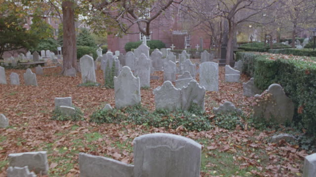 MEDIUM ANGLE CEMETERY.  SEE HEADSTONES IN REAR OF CHURCH. SEE RED BRICK CHURCH. PAN UP, SEE TOWER WITH STEEPLE AND ARCHED WINDOWS UP SIDE OF TOWER.