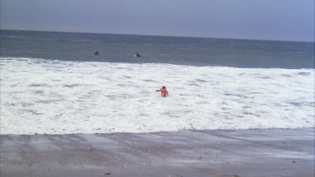 WIDE ANGLE OF YOUNG WOMAN IN RED ONE PIECE BATHING SUIT RUNNING DOWN SHORE WITH SURFBOARD TOWARDS OCEAN. SHE BEGINS PADDLING OUT TOWARDS OTHER SURFERS WAITING FOR WAVES.