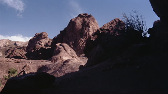 MEDIUM ANGLE OF RUST COLORED ROCKS AND BOULDERS WITH SOME DRY WEEDS THROUGHOUT. COULD BE DESERT. SEE FOREGROUND IN SHADE. SEE SOME CLOUDS AND BLUE SKY IN BACKGROUND.