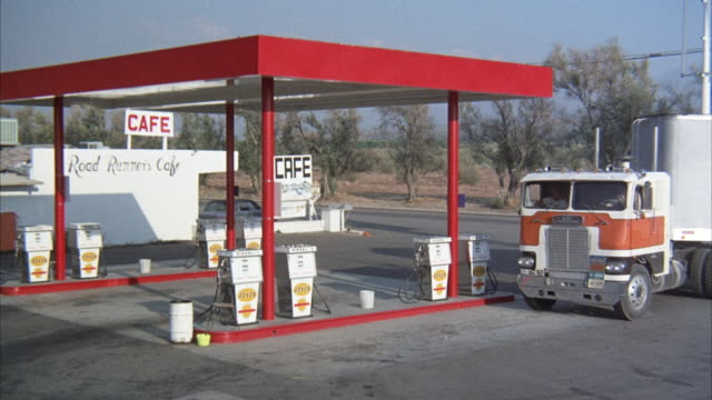 "MEDIUM ANGLE OF RED GAS STATION. SEE GREY BIG RIG WITH WHITE AND ORANGE CAB AND ""STS"" ON SIDE PULL UP IN FRONT OF GAS PUMP. SEE PASSENGER GET OUT AND DRIVER DOOR OPEN."