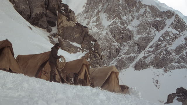 medium angle of man standing along row of tents on snowy mountain slope. see man holding coil of rope as fierce wind blows from left. see snowy mountain slopes in background. - rope stock videos & royalty-free footage